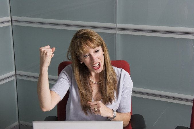 A professional woman sitting at a desk looking at her computer celebrating with a smile and a fist pump.